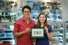 Portrait Of Happy Shop Owners Showing First Dollar Earning Stock Photos
