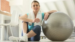 Mature woman drinking water, sitting by fitness ball Stock Footage