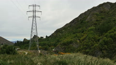 New Zealand Kawarau River power line tower near rugged hill Stock Footage