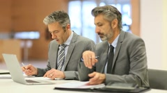 Businessmen working on laptop computer Stock Footage