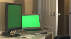Man sits down then browses dual computer monitors -green screen Stock Footage