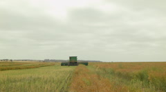 Combine Harvester Driving Away While Swathing a Canola Crop for Harvest Stock Footage