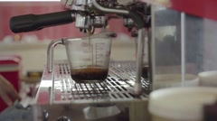 Fresh roasted coffee are being squeezed into a measuring cup Stock Footage