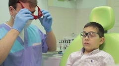 Young boy having a check up at dentist's surgery. Patient lying on exam chair Stock Footage