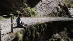 Trekking - break to eat something, on the edge of the paved path Stock Footage