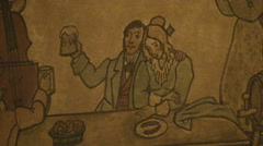 Bar scene wood engraving on wall, man holding beer Stock Footage