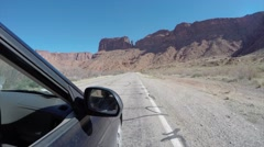 The high exterior shot of a car driving in a desert Stock Footage