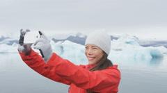 Girl taking selfie photo by Jokulsarlon Iceland - Happy tourist on travel Stock Footage