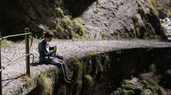 Trekking - break to drink, sitting on the edge of the paved path Stock Footage
