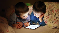 Cute little brothers, playing on tablet in bed at night Stock Footage