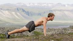 Pushups fitness man doing push ups outside nature - cross training workout Stock Footage