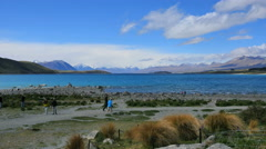 New Zealand Lake Tekapo tourists and rock strewn shore Stock Footage