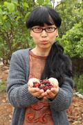 Happy woman holding mulberries and grimacing Stock Photos