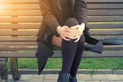 Young hipster Woman Sitting on Bench part of the body image backlit - stock photo