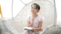 Little asian girl thinking and writing notebook - stock footage