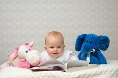 Baby girl reading a book Stock Photos