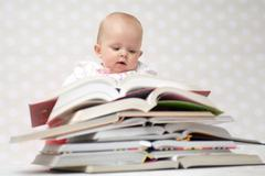 Baby with pile of books - stock photo