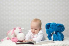 Baby girl reading a book - stock photo