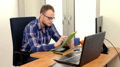Men, siting behing his desk and alternately using tablet and smartphone, Stock Footage