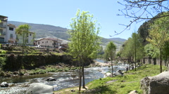 River at a meander by the town, with trees and people cleaning Stock Footage