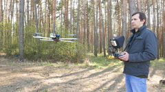 Man drone operator  operate by copter in sunny wood. 4K 3840x2160 Stock Footage