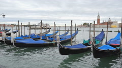 Parked Gondolas bobbing in the water as a water taxi passes behind - Venice, Stock Footage