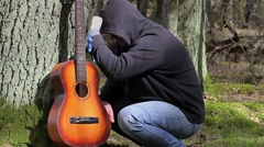 Stressful Man with guitar in the forest near tree Stock Footage
