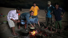 People cooking inside the cave Stock Footage