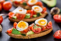 Bruschetta with tomato, avocado and quail egg - stock photo