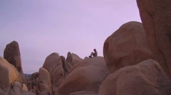 Distant Boy Sitting On Rock At Dusk- Joshua Tree National Park Stock Footage