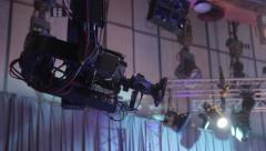 A camera is suspended from the crane moves across the TV Studio. Live broadcast Stock Footage