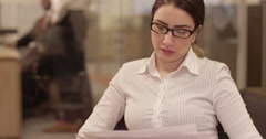 Tired businesswoman with a concerned look working at a modern glass office. Stock Footage