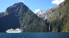 New Zealand Milford Sound cruise ship passing Stirling Falls Stock Footage