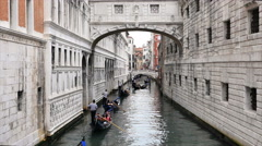 Gondolas under Bridge of Sighs along narrow Rio di Palazzo canal - Venice, Italy Stock Footage