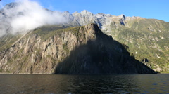 New Zealand Milford Sound passing overhanging precipice Stock Footage