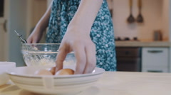 Woman cracking eggs in the kitchen Stock Footage