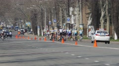 Collegiate cyclists take a ride in criterium bike race through the streets of Stock Footage