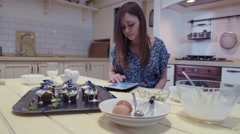 Young woman using a digital tablet to cook with, scrolling through a recipe - stock footage