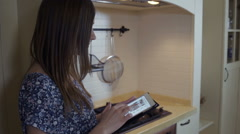 Young woman using a digital tablet to cook with, than check the oven - stock footage