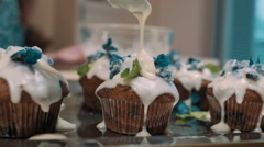 Close up feminine hands decorating cupcakes, slow motion Stock Footage
