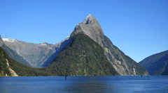 New Zealand Milford Sound Mitre Peak with green hill in front Stock Footage