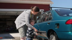 Mother washing a car with her cute toddler Stock Footage