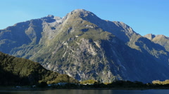 New Zealand Milford Sound moutain and white buildings at foot Stock Footage