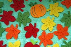 Bright Maple leaves out of felt on a light green fabric as a background Stock Photos