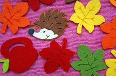 Hedgehog and colorful Maple leaves out of felt on a pink fabric as a backgrou Stock Photos
