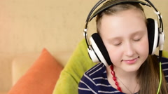 Innocent teenage girl enjoy to listen music with big headphone at home Stock Footage