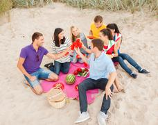 group of happy friends having picnic on beach - stock photo