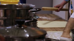 Chefs hands unrolling dough with a rolling pin in kitchen Stock Footage