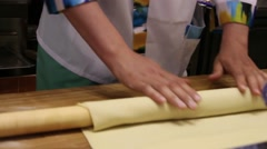 Male chefs hands preparing dough with rolling pin for asian food on wooden board Stock Footage