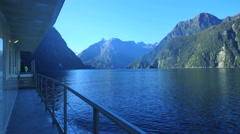 New Zealand Milford Sound reflective water flows past ship Stock Footage